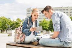 Jovem mulher com o amigo masculino que usa a tabuleta digital no terreno da faculdade foto de stock royalty free