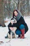Jovem mulher com o cão ronco no parque do inverno imagens de stock