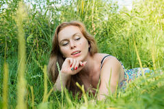 Jovem mulher com o cabelo longo que encontra-se na grama no verão Imagens de Stock