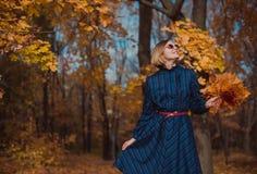 Jovem mulher com o cabelo louro que veste o vestido azul que anda no parque do outono fotografia de stock
