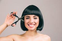 Jovem mulher com o cabelo preto que levanta na c?mera Morena agradável alegre com sorriso do corte de cabelo do prumo Vista reto  foto de stock