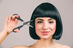 Jovem mulher com o cabelo preto que levanta na c?mera Morena segura agradável alegre com o corte de cabelo do prumo que olha em l foto de stock