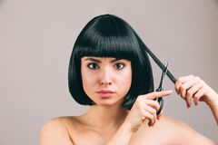 Jovem mulher com o cabelo preto que levanta na c?mera Morena segura séria com corte de cabelo do prumo Guardando tesouras e corte fotografia de stock