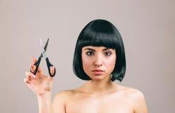 Jovem mulher com o cabelo preto que levanta na c?mera Vista em linha reta Guardar scissors ? disposi??o Morena séria com prumo imagem de stock