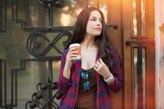 Jovem mulher com o café a ir exterior na cidade Fotos de Stock Royalty Free