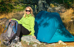 Jovem mulher com o caminhante de sorriso da cara que senta-se com o acampamento da trouxa e da barraca exterior Imagem de Stock
