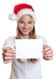 Jovem mulher com o chapéu do Natal que mostra o cartão vazio Fotos de Stock Royalty Free