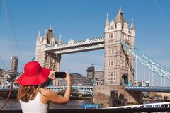Jovem mulher com o chap?u vermelho que toma uma foto da ponte da torre em Londres imagem de stock