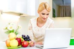 Jovem mulher com o computador portátil na cozinha Foto de Stock Royalty Free