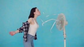 Jovem mulher com o fã elétrico que aprecia o vento fresco video estoque