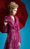 Jovem mulher com o guarda-chuva no azul foto de stock