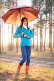A jovem mulher com o guarda-chuva no por do sol ilumina-se na floresta Fotografia de Stock Royalty Free