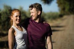 Jovem mulher com o homem que está na exploração agrícola no dia ensolarado fotografia de stock royalty free