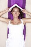 Jovem mulher com o livro guardando fechado dos olhos ao encontrar-se na cobertura do piquenique Imagens de Stock