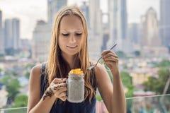 Jovem mulher com o mehendi da hena disponível que come o pudim do chia em seu balcão que negligencia a cidade grande imagens de stock