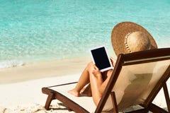 Jovem mulher com o PC da tabuleta na praia Foto de Stock