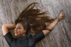 Jovem mulher com o penteado bonito que encontra-se no assoalho Vista superior foto de stock