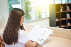 Jovem mulher com o planejador na estudante universitário na biblioteca fotografia de stock royalty free