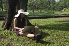 Jovem mulher com o portátil na grama no parque imagem de stock