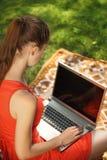 Jovem mulher com o portátil na grama verde no parque Foto de Stock