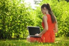 Jovem mulher com o portátil na grama verde no parque Imagens de Stock