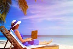 Jovem mulher com o portátil na praia tropical Foto de Stock Royalty Free