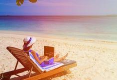 Jovem mulher com o portátil na praia tropical Imagem de Stock