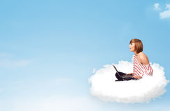 Jovem mulher com o portátil que senta-se na nuvem com espaço da cópia Imagens de Stock