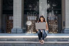 Jovem mulher com o portátil que senta-se nas escadas, perto da universidade Fotos de Stock