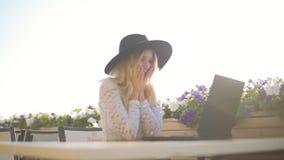 Jovem mulher com o portátil que senta-se no café perto do mar, e trabalho vídeos de arquivo