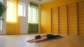 Jovem mulher com o samakonasana praticando da ioga da aparência oriental apenas no estúdio amarelo minimalista Menina que faz a video estoque