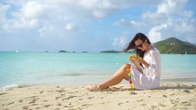 Jovem mulher com o smartphone durante férias tropicais da praia Menina bonita na praia com o telefone celular nas Caraíbas vídeos de arquivo