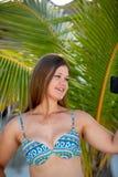 Jovem mulher com o smartphone na frente da palma fotografia de stock