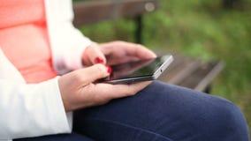 Jovem mulher com o smartphone no parque Deslize o slider filme