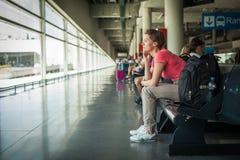 Jovem mulher com o telefone celular que espera um ônibus na estação imagens de stock royalty free