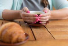 Jovem mulher com o tratamento de mãos cor-de-rosa que guarda um copo do chá verde, nenhuma cara Imagem de Stock