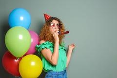 Jovem mulher com o ventilador do partido perto dos balões no fundo da cor Celebração do aniversário Fotos de Stock