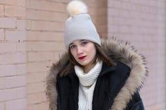 Jovem mulher com olhos azuis e gola alta branca vestindo do batom vermelho sob o revestimento morno do inverno fotos de stock royalty free