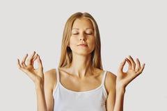 Jovem mulher com olhos fechados e mãos no gesto dos lótus Conceito da meditação, do equilíbrio e da paz de espírito Isolado sobre foto de stock