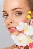Jovem mulher com orquídea, no fundo branco Imagem de Stock Royalty Free