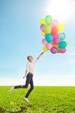 Jovem mulher com os balões nas mãos no campo contra o céu Fotos de Stock