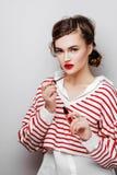 Jovem mulher com os bordos vermelhos na cara emocional bonita no vestido elegante que guarda o batom da composi??o no est?dio fotografia de stock royalty free