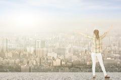 Jovem mulher com os braços esticados que olham a cidade Imagens de Stock