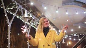 Jovem mulher com os chuveirinhos no fundo da cidade da noite filme