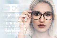Jovem mulher com os espetáculos no fundo da carta de teste da visão Imagem de Stock Royalty Free