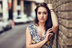 Jovem mulher com os olhos azuis que estão ao lado da parede de tijolo fotos de stock
