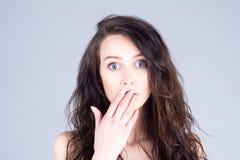 A jovem mulher com os olhos muito grandes na surpresa cobre a boca com a mão Foto de Stock Royalty Free
