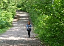Jovem mulher com os pés descalços em uma estrada de floresta Imagens de Stock Royalty Free