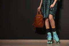 Jovem mulher com os patins de rolo retros contra a parede preta, close up fotos de stock royalty free