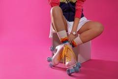 Jovem mulher com os patins de rolo retros no fundo da cor, close up imagens de stock royalty free